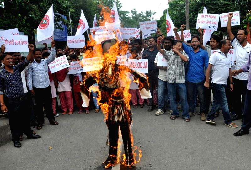 All Assam Student's Union (AASU) activists burn an effigy of Assam Chief Minister Tarun Gogoi during a demonstration in Guwahati on Aug 13, 2014. - Tarun Gogoi