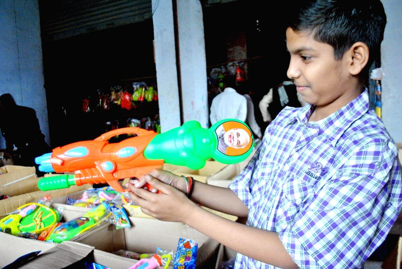 A child buys color sprinklers with a picture of Prime Minister Narendra Modi in Allahabad, on March 1, 2015. - Narendra Modi