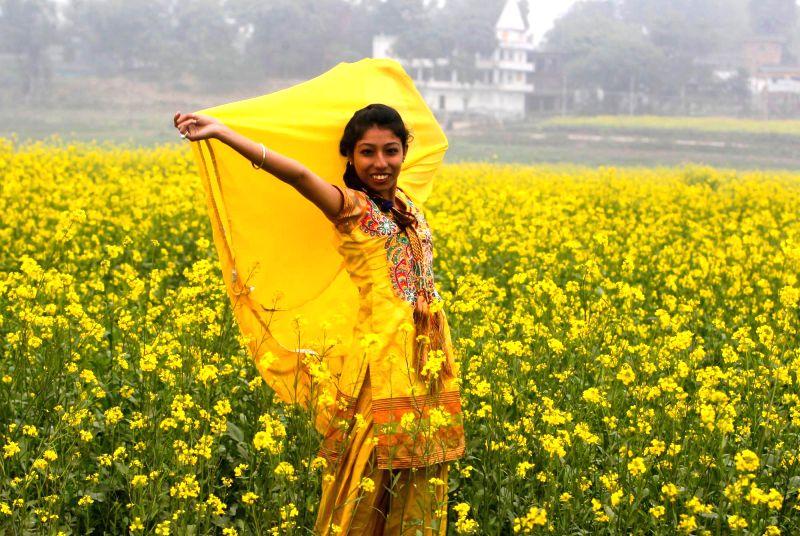 A girl celebrates Lohri in mustard fields near Allahabad on Jan 13, 2015.