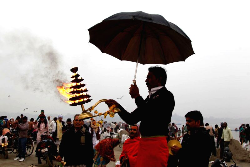 A Hindu priest holds an umbrella as he performs morning aarti on new year at Sangam in Allahabad, on Jan 1, 2015.