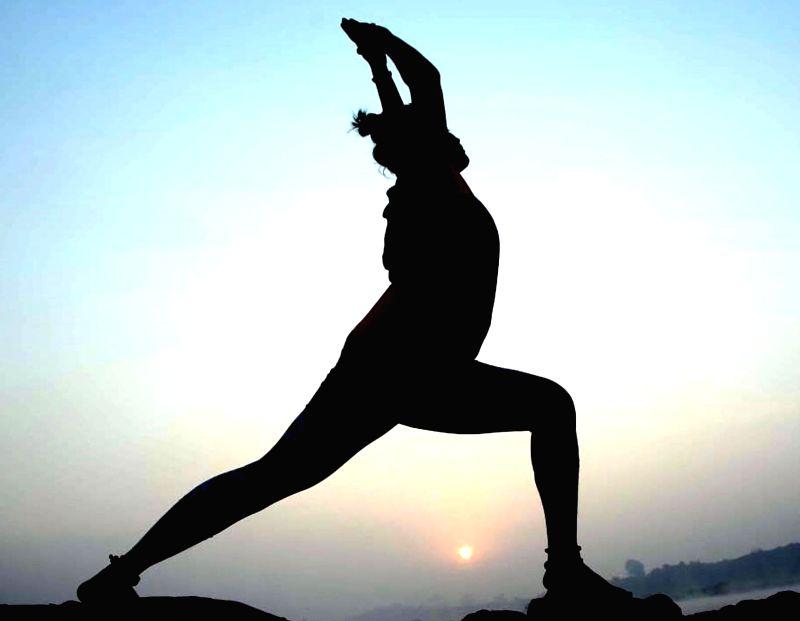 Allahabad:  A lady practices yoga 'asanas' at Sangam at sunrise in Allahabad.