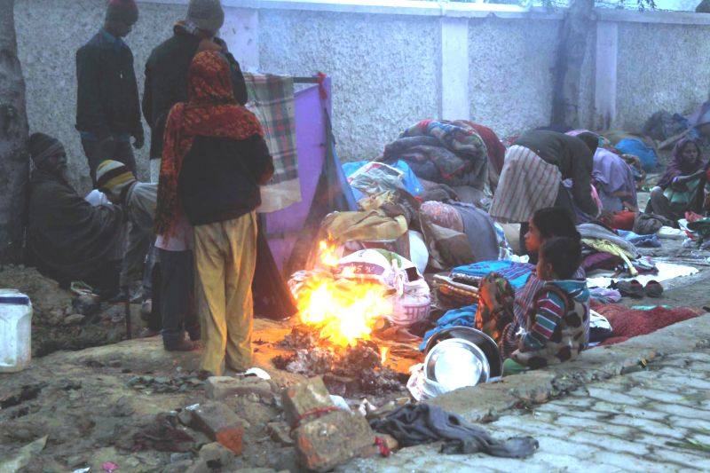 Homeless people sit around a fire lit on a pavement to keep themselves warm on a foggy day in Allahabad, on Dec 29, 2014.