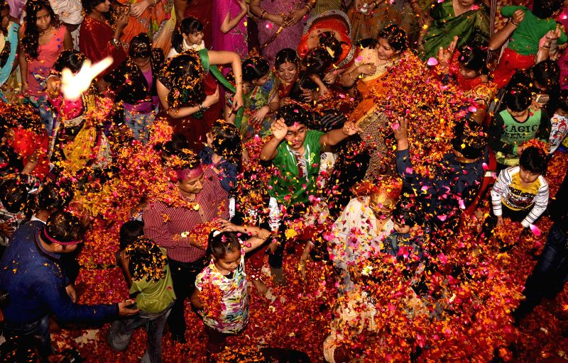People play Holi with flower petals in Allahabad, on March 1, 2015.