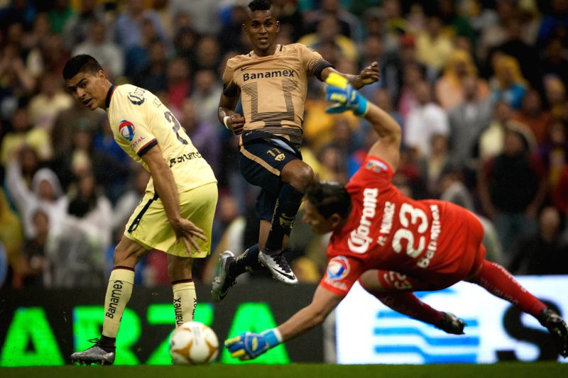 America's goalkeeper Moises Munoz (F) tries to catch the ball during the Semi-Finals of the Opening Tournament of the MX League against Pumas de la UNAM, at ...
