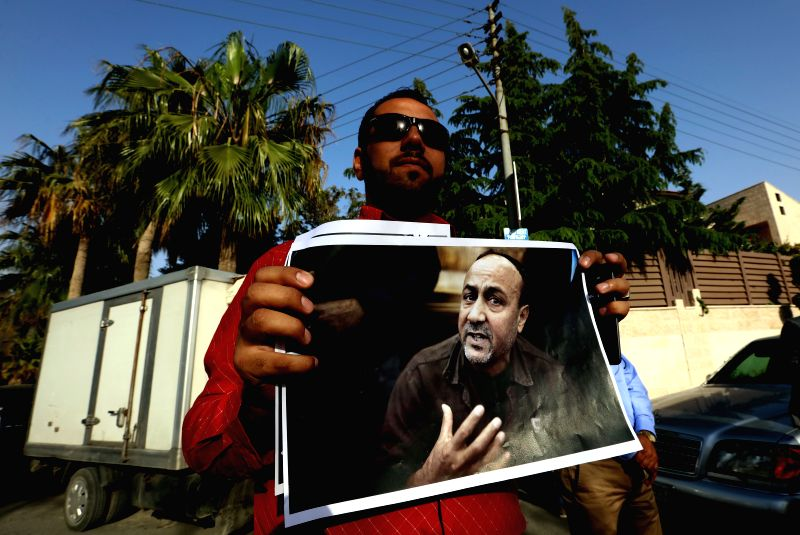 AMMAN, April 27, 2017 - A Jordanian man holds the picture of Marwan Barghouti, one of the Palestinian prisoners, during a protest in front of International Committee of the Red Cross in Amman, ...