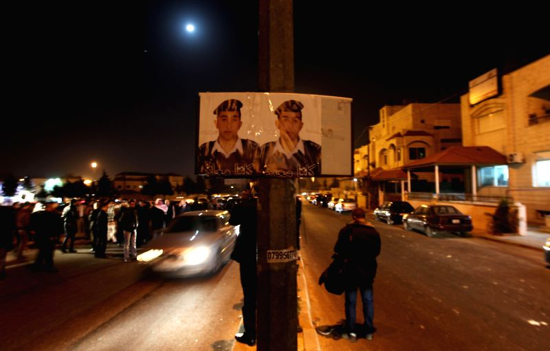 People walk past a poster of the Jordanian pilot Moaz al-Kasasbeh after the release of a video purportedly showing Islamic State captive Jordanian pilot being burnt ...