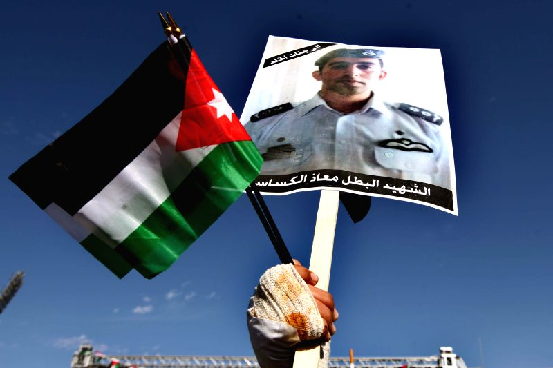 A Jordanian holds a picture of Jordanian pilot Muazth al-Kassasbeh during a rally against the Islamic State (IS) in Amman, Jordan, Feb. 5, 2015. Jordanians gathered ... - Abu Ghosh