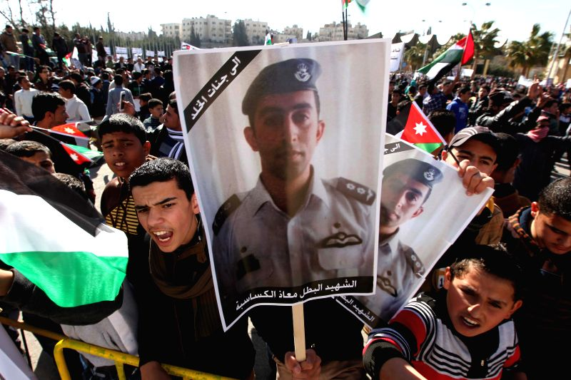 Jordanians hold pictures of Jordanian pilot Muazth al-Kassasbeh during a rally against the Islamic State (IS) in Amman, Jordan, Feb. 5, 2015. Jordanians gathered ... - Abu Ghosh