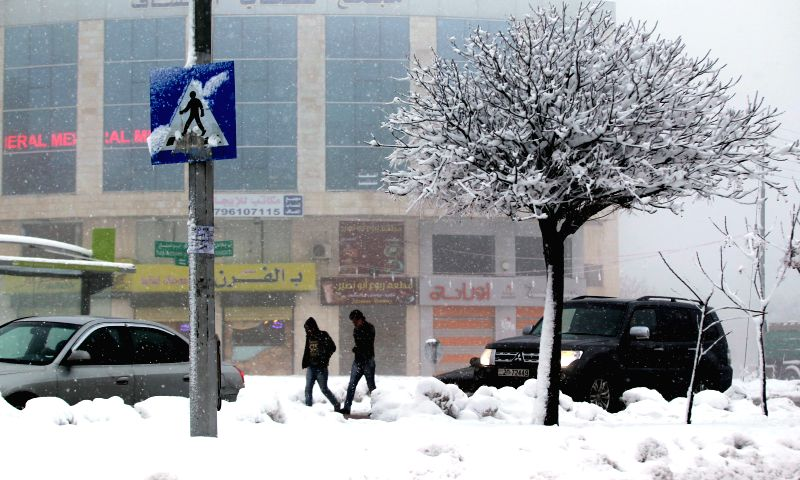 Jordanian men walk through a street covered with snow during a snowstorm in Amman, Jordan, Jan. 9, 2015.