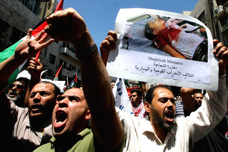 Locals shout slogans during a protest against Israeli air strikes on Gaza, in front of Al-Husseini Mosque in downtown Amman, Jordan, July 25, 2014.(Xinhua/Mohammad ...