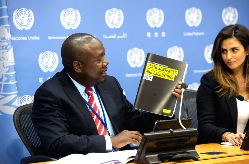 Amnesty International Senior Director for Law and Policy Tawanda Mutasah hold up the Global Report on Death Sentences and Executions 2017 at a briefing he and the organisation's New York ...
