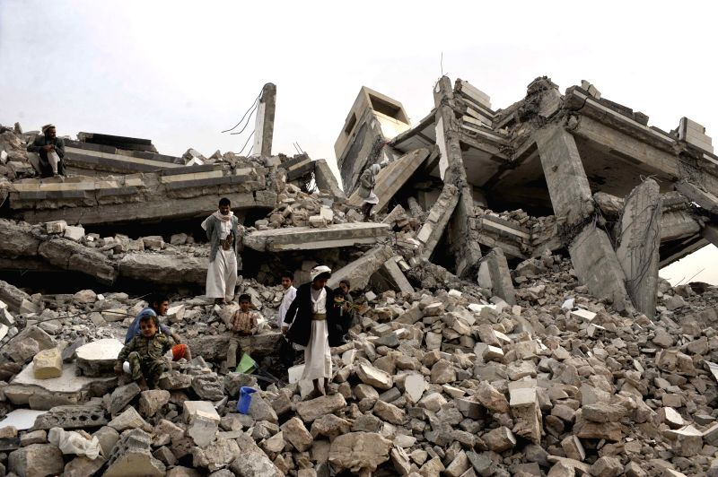 Yemeni stand near the wreckage of a five-story building that was destroyed in the conflicts between the Shiite Houthi rebels and the Yemeni army troops in Amran city,