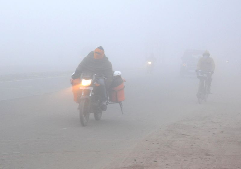 A bike runs with its headlights on as dense fog covers Amritsar on Dec 18, 2014.
