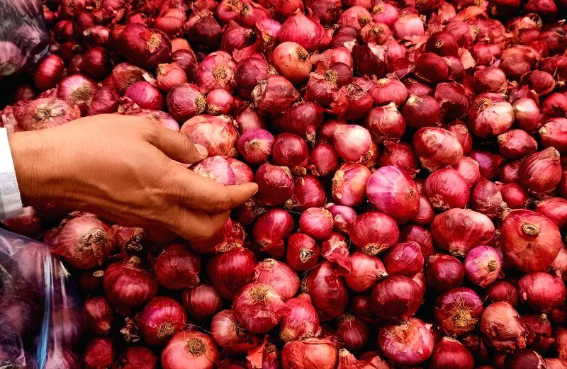 Amritsar: A vendor sorts onions for sale at a roadside in Amritsar on Saturday on Saturday 27th February, 2021.(Photo: Pawan Sharma/IANS)