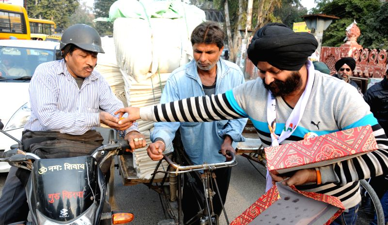 An Aam Aadmi Party (AAP) worker distributes sweets as he celebrates party's victory in the recently concluded Delhi Assembly Polls in Amritsar, on Feb 10, 2015.
