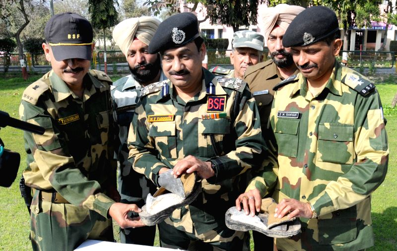 Border Security Force officials show  a pair of sandals containing nearly 500 gm of heroin recovered near Indo-Pak border, Amritsar, on Feb 13, 2015. The sandals were thrown by a Pakistani .