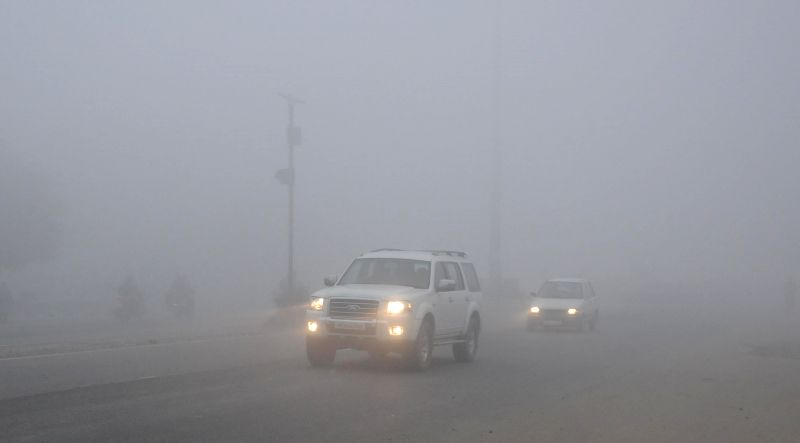 Cars runs with their headlights switched on as dense fog covers Amritsar on Dec 18, 2014.