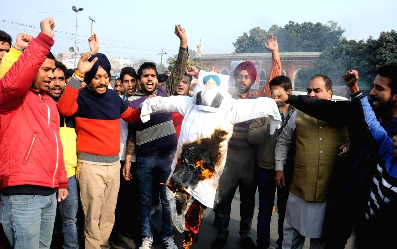 Congress workers burn an effigy of senior Akali leader Virsa Singh Valtoha during a demonstration in Amritsar on Dec 24, 2014.