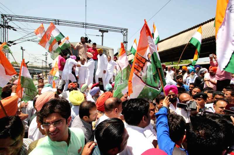 Congress workers stage a demonstration on the railway tracks at Amritsar railway station hold cut-outs of their demands that include relaxation in procurement norms and compensation for ...