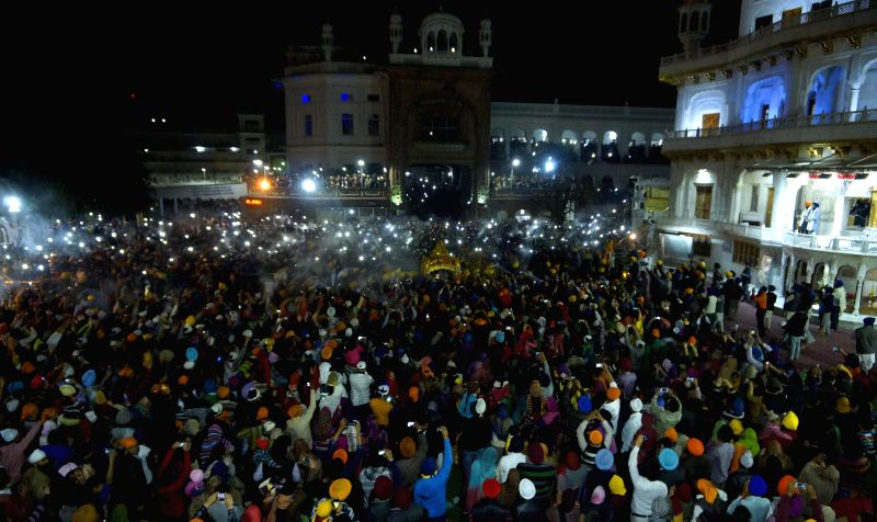 Devotees spray perfume on Palki Sahib - the palanquin that carries the holy scriptures of Sikhism during `Hola Mohalla` celebrations at the Golden Temple in Amritsar, on March 6, 2015.
