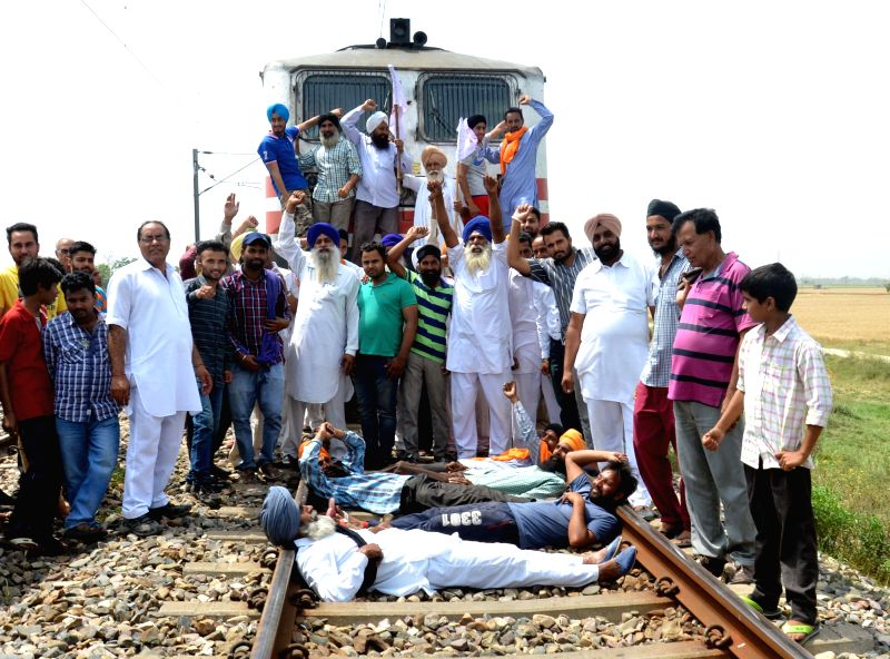 Farmers stage a demonstration on railway tracks to press for their various demands including relaxation in procurement norms and compensation for loss of crops  in Amritsar of Punjab, on ...
