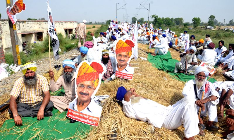 Farmers staging a demonstration on the railway tracks near Amritsar hold cut-outs of Aam Aadmi Party (AAP) leader Arvind Kejriwal after the the party backed their demands that include ... - Arvind Kejriwal