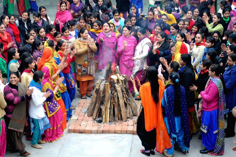 Girls wearing traditional Punjabi dresses celebrate Lohri in Amritsar on Jan 13, 2015.