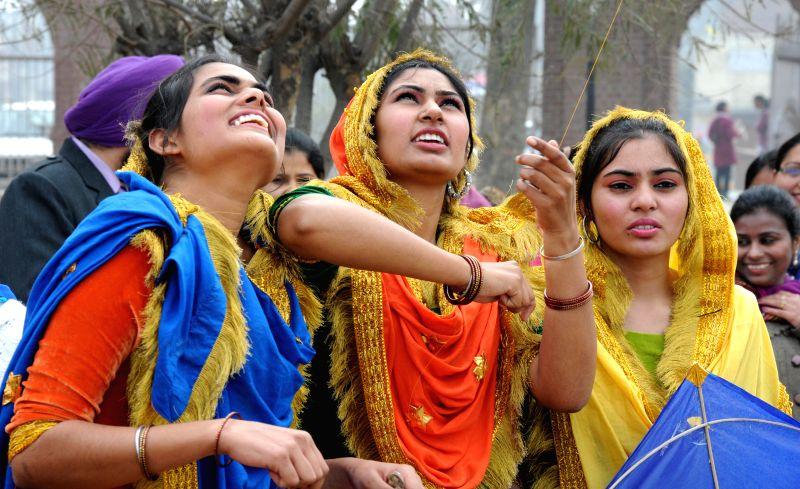 Girls wearing traditional Punjabi dresses fly kites on Lohri in Amritsar on Jan 13, 2015.
