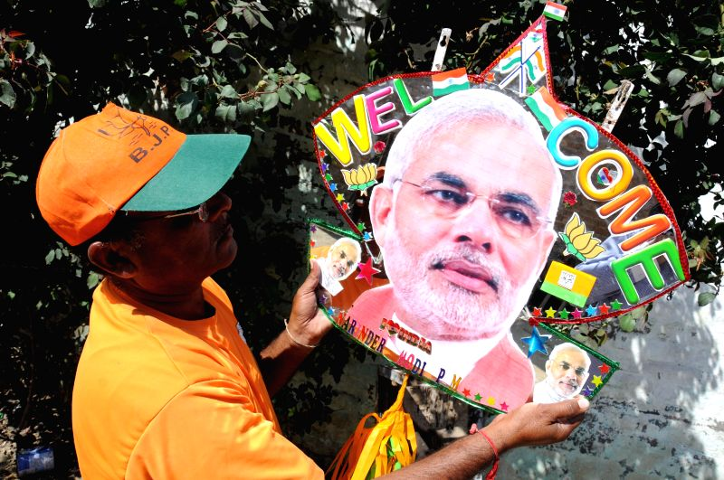 Kite maker Jagmohan Kanojia showing a glass (mirror) kite with photograph of PM Modi ahead of his arrival in the city on March 22, 2015.