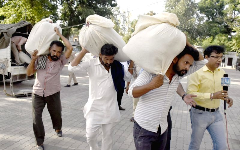 Amritsar: Labors seen carrying 500 kg heroin, valued at around Rs 2,700 crore to court in Amritsar, on June 30, 2019. The Customs seized the heroin at the Integrated Check Post at the Attari border. (Photo: IANS)