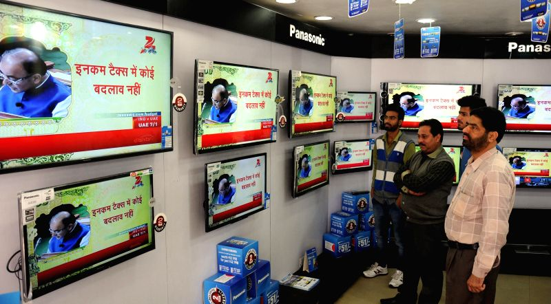 People watch Union Finance Minister Arun Jaitley present national budget 2015-16 on television sets in an electronics showroom in Amritsar, on Feb 28, 2015. - Arun Jaitley