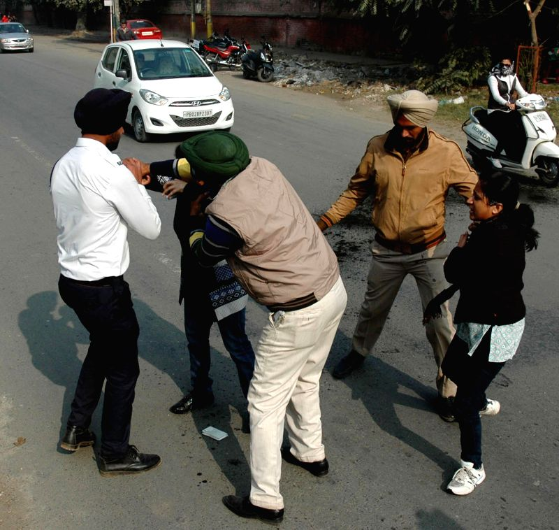 Police personnel try to stop two women who attemped  self-immolation in front of the office of Punjab Police Commissioner by sprinkling kerosene oil on themselves in Amritsar on Dec 16, ...