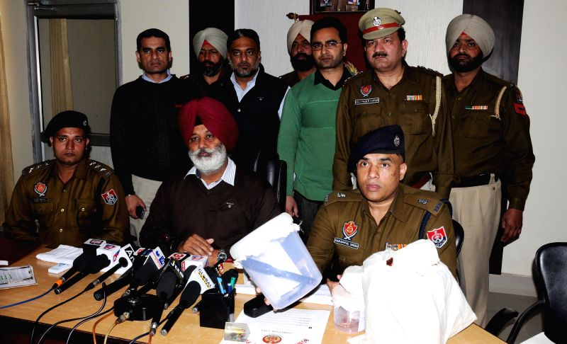 Policemen present before press 3 kg heroin - worth Rs. 15 crores in the international market - seized from smugglers during a press conference in Amritsar on March 10, 2015.