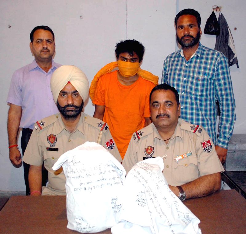 Policemen present before press the smugglers arrested with 2 kg heroin - worth Rs. 10 crores in the international market - in Amritsar, on April 4, 2015.