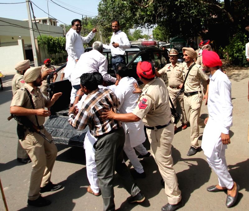 Policemen take away Congress workers staging a demonstration against BJP chief Amit Shah in Amritsar on May 2, 2015.