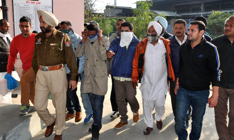 Policemen take away the smugglers who were held with 3kg heroin in Amritsar, on Feb 27, 2015.