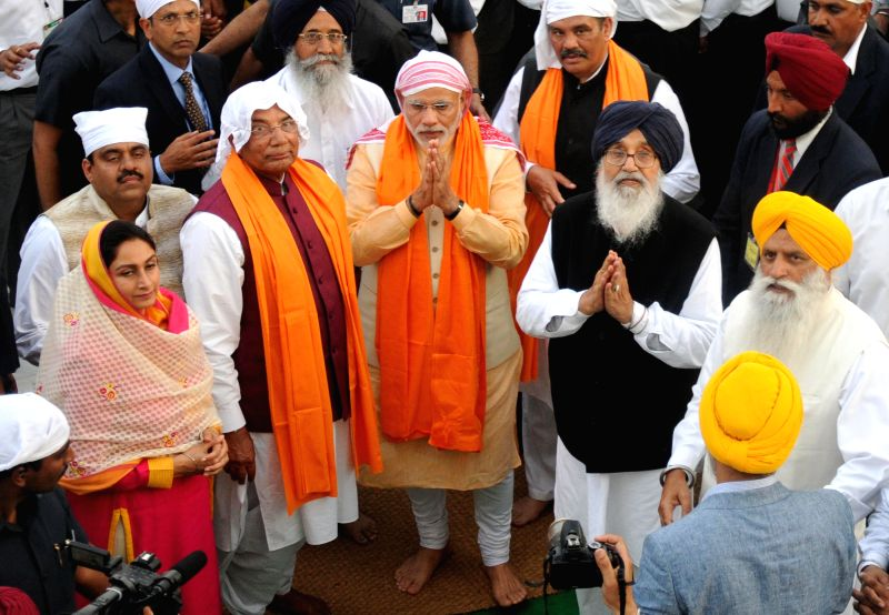 Prime Minister Narendra Modi pays obeisance at the Golden Temple, in Amritsar, Punjab on March 23, 2015. Al;so seen Punjab Chief Minister Parkash Singh Badal. - Narendra Modi and Parkash Singh Badal