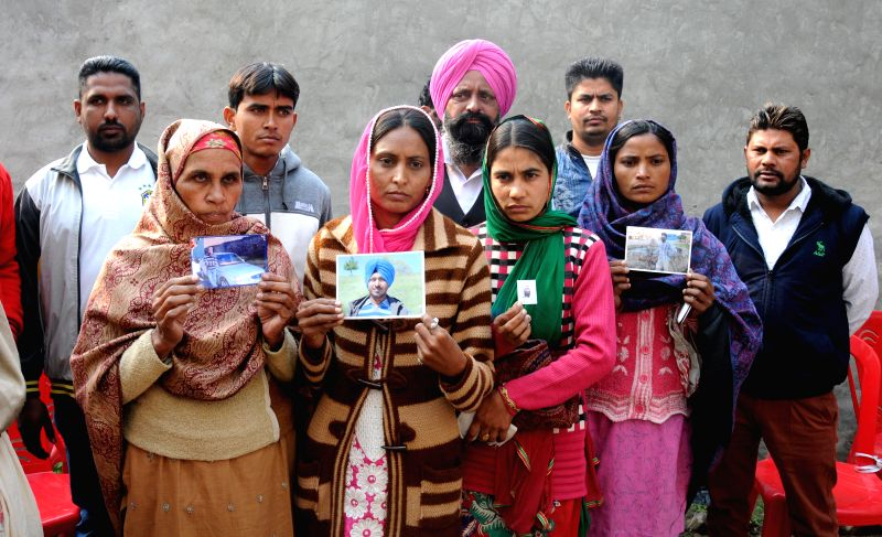 Relatives of Indian workers who were taken hostage in Iraq pose with photographs bearing their image in Amritsar on Dec. 13, 2014.