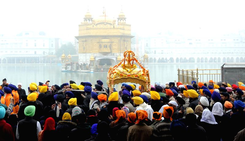 Sikh devotees participate during a religious procession at the Golden Temple on the eve of birth anniversary of 10th Sikh Guru Gobind Singh Ji in Amritsar on Dec 27, 2014.