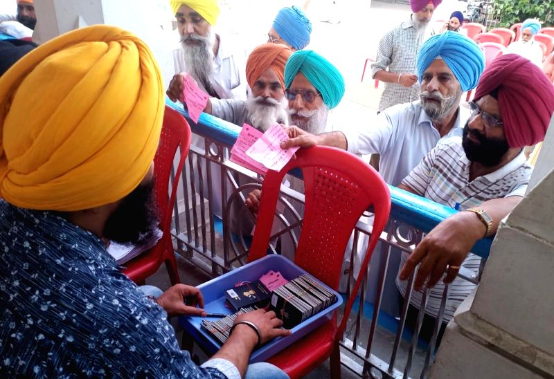 Amritsar: Sikh devotees show their visas as they would leave for Pakistan to observe the death anniversary of Maharaj Ranjit Singh via Attari international rail border in Amritsar on June 26, 2019. (Photo: IANS)