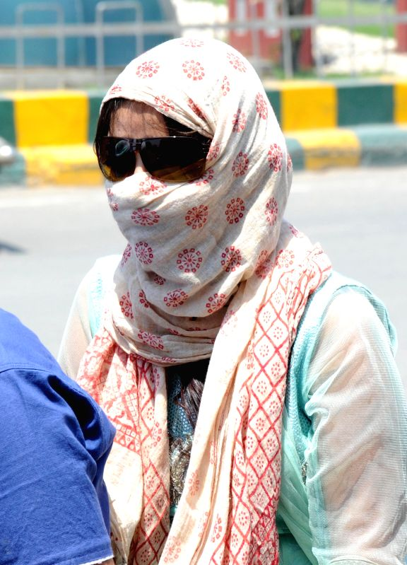 Women cover their faces so as to avoid scorching sun in Amritsar on May 16, 2015.