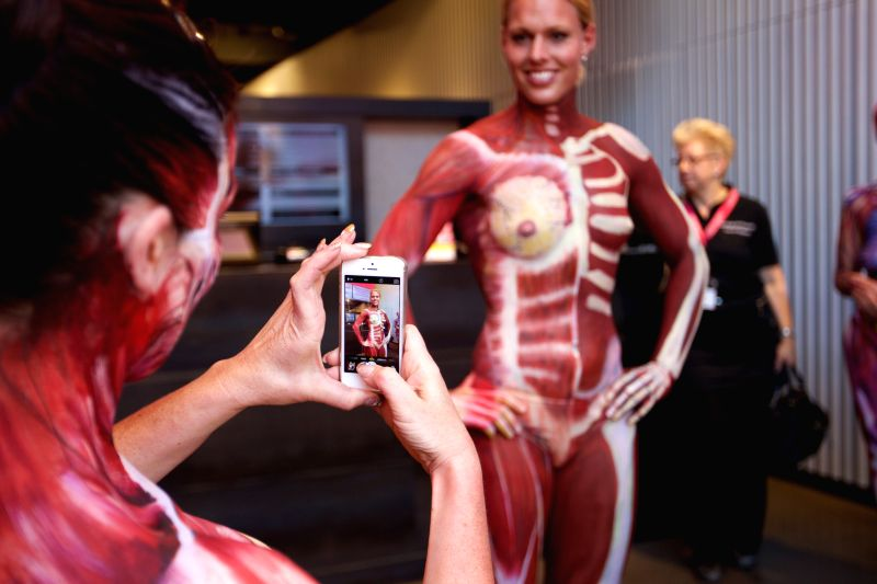 """A model takes photos of her peer's body painting during """"Under Your Skin"""", an exhibition featuring anatomical body paintings, at Dam Square in downtown ..."""