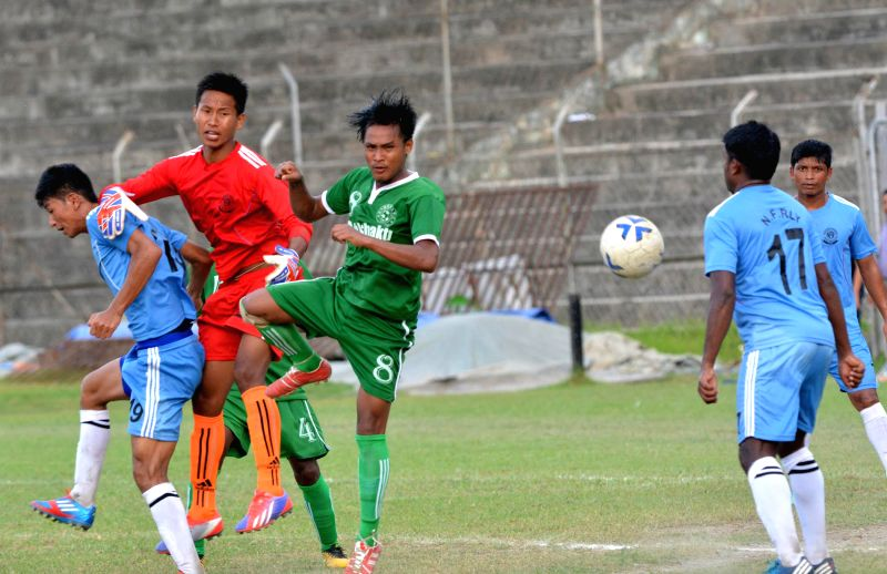 An action moment during the 10th NN Bhattacharya Football Tournament played between Kamrup Football Club (green jersey) and N.F. Railway Sports Club (blue jersey) organised by Guwahati Sports ...