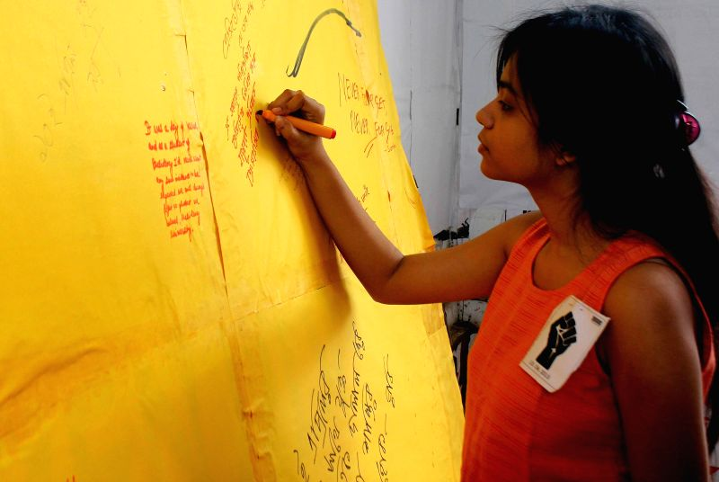 An activist of SFI writes on a poster to protest against West Bengal Government at Presidency College in Kolkata on April 10, 2014.