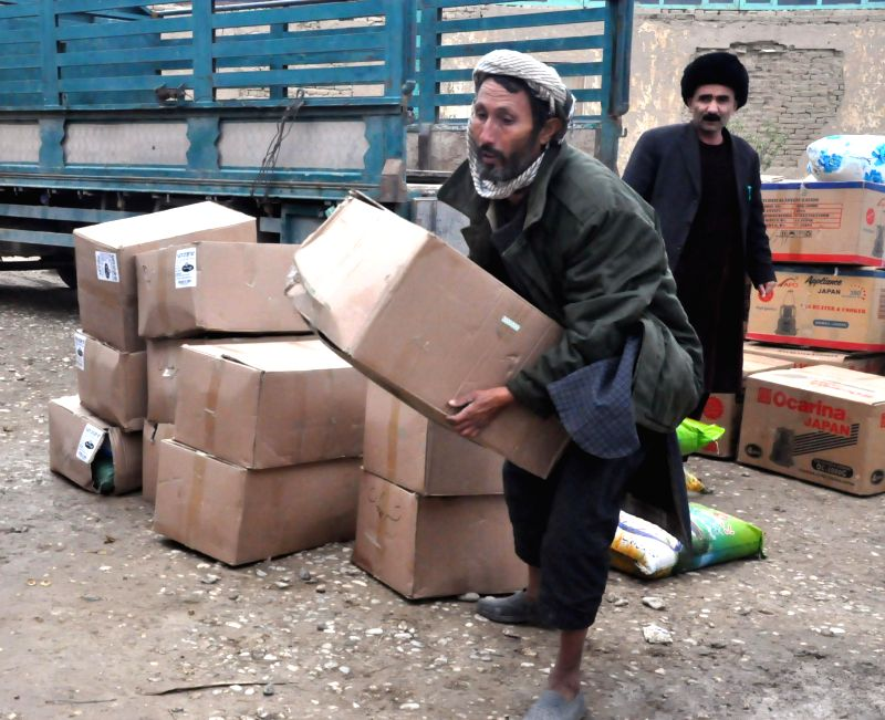 An Afghan man receives winter relief materials distributed by Afghan government in Jawzjan province, Afghanistan, Nov. 24, 2015. The Afghan government and aid ...