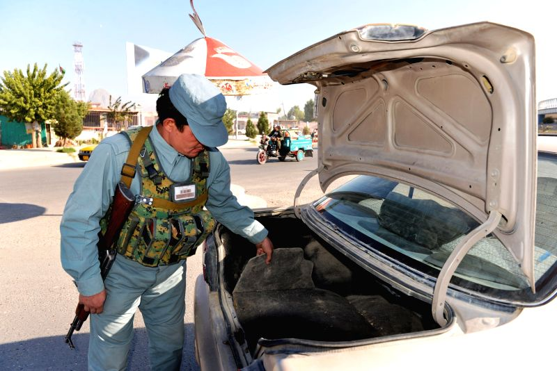An Afghan policeman searches a vehicle at a police checkpoint in Kandahar province of southern Afghanistan, Nov. 21, 2015.