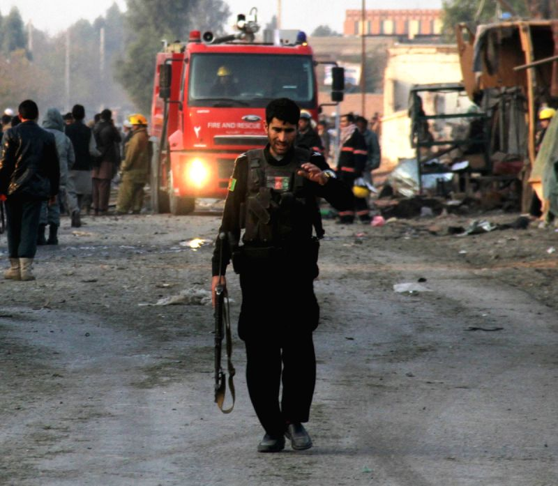 An Afghan policeman walks at the site of a suicide attack in Surkh Rod district of Nangarhar province, east Afghanistan, Dec. 7, 2015. At least 12 people including ...