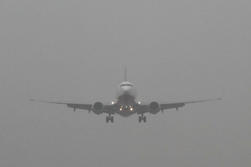 An aircraft attempts landing at an airport on a foggy day.