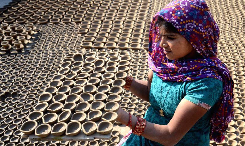An artisan busy making earthen lamps ahead of Diwali in Amritsar, on Nov 2, 2015.