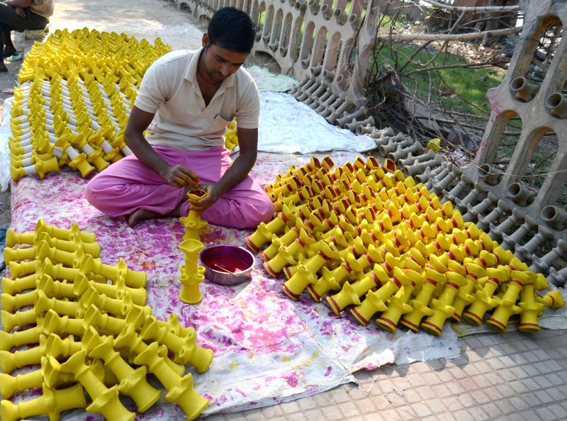 An artisan busy painting earthen lamps ahead of Diwali in Amritsar, on Nov 2, 2015.